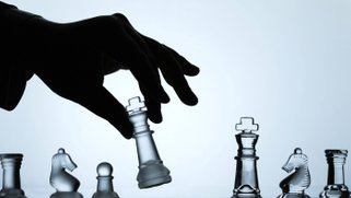 Artistic photo of a hand moving a chess piece on a chessboard.