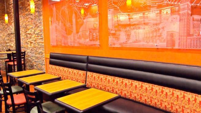 Photo inside a DiPasqua owned Subway restaurant showing tables, a bench, and glass artwork on the wall.