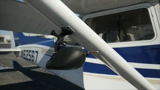 Picture of a wingBug device mounted to the wing of an airplane.