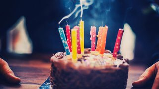 A small cake with candles blown out - smoke coming off the colorful candles